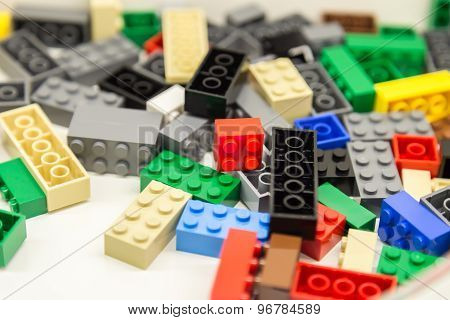 Pile of colorful building blocks with selective focus and highlight few particular block