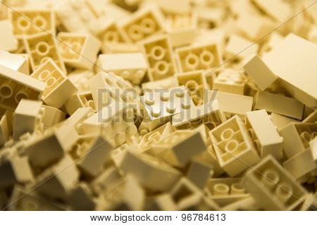 Pile of beige white color building blocks with selective focus and highlight on one particular block
