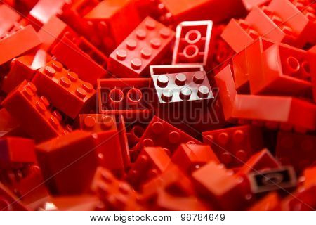 Pile of red color building blocks with selective focus and highlight on one particular block