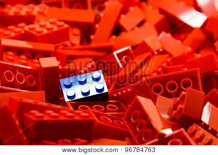 Pile of red color building blocks with selective focus and highlight on one particular blue block
