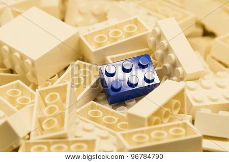 Pile of white color building blocks with selective focus and highlight on one particular blue block