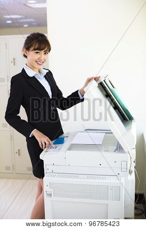 pretty young secretary using photocopy machine in office