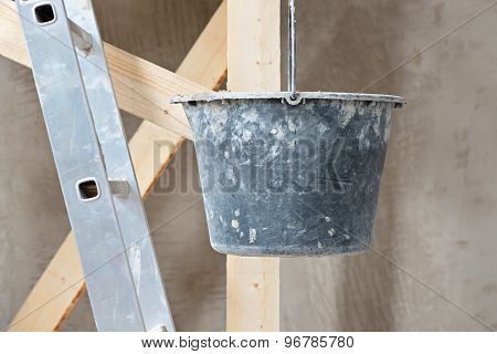 Dirty bucket and ladder on wall background