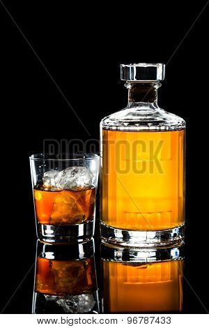 Iced cold whiskey on the rocks and a whiskey bottle in dark background in portrait orientation