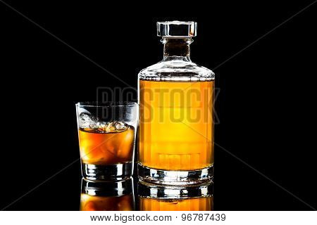 Iced cold whiskey on the rocks and a whiskey bottle in dark background