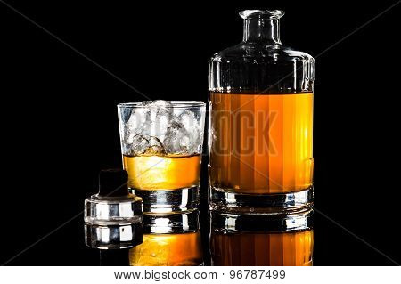 Whiskey on the rocks and a bottle of whiskey with cork on table in dark background