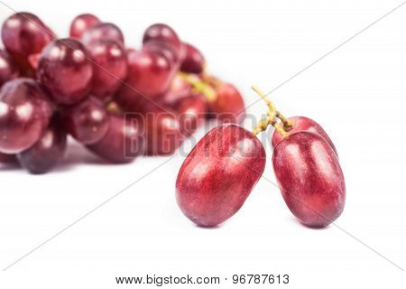Three pieces of juicy red crimson grape with de-focused bunches in the background