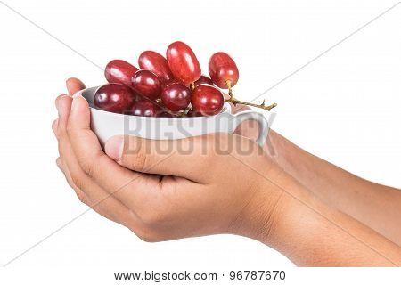 Hand holding cup full of juicy, seedless and sweet red crimson grapes