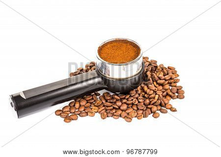 Coffee portafilter filled with finely grounded coffee, and with coffee beans scattered around