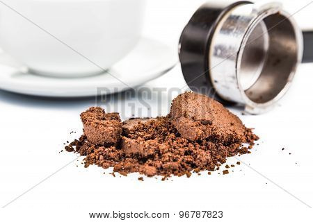 Spent or used coffee grounds with portafilter and a cup of freshly brewed coffee in the background