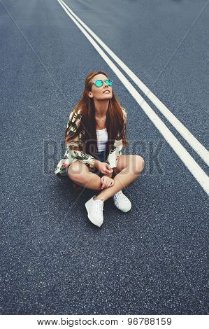 Charming Californian hipster girl sitting on her cruiser longboard in the middle of asphalt road