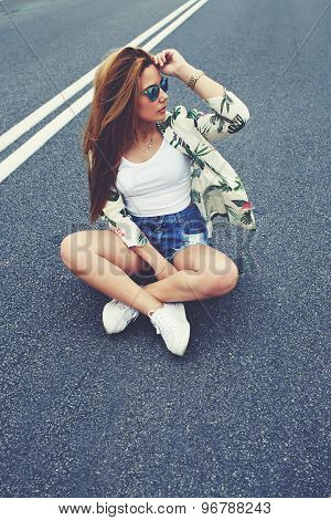 Beautiful Californian hipster girl sitting on her cruiser longboard in the middle of asphalt road