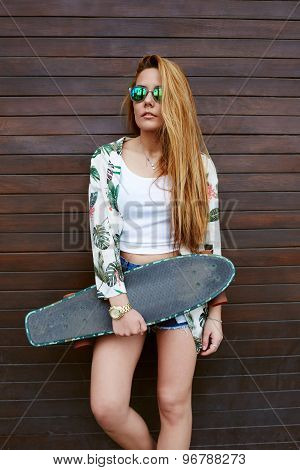 Casually-dressed female hipster with beautiful figure posing with longboard in summer