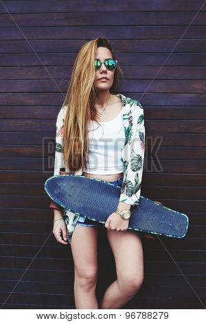 Portrait of casually-dressed female hipster holding skateboard while she standing on wooden wall