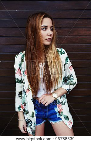 Beautiful hipster girl wearing trendy clothing posing on wooden wall background while looking away