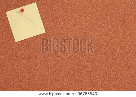 Cork board with yellow note and red pin
