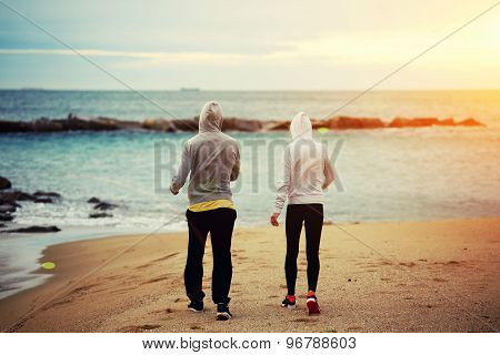 Young couple of runners walking on the beach resting after intense morning training together