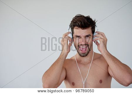 handsome young man listening music on headphones at modern home over  white wall and standing on hands