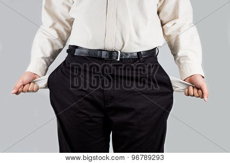 Man in office wear pulling out empty pockets from his pants