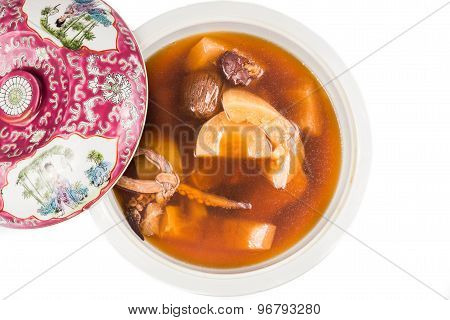 Pot of delicious and nutritious Chinese old cucumber soup isolated in white