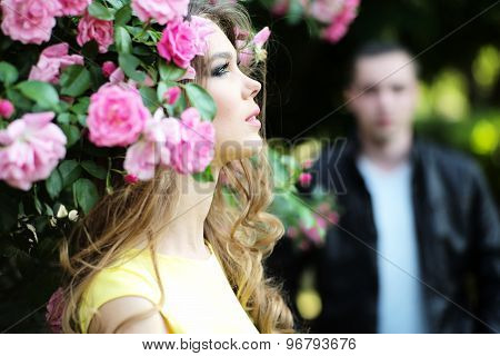 Blonde And Man Near Rose Bush