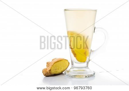 Hot ginger tea in glass with a piece of ginger root