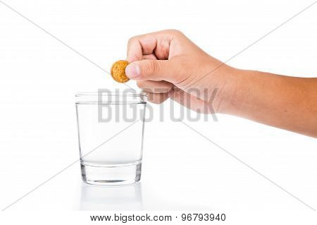 Hand dropping effervescent vitamin C tablet into glass of water
