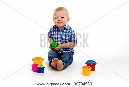 Happy Baby In A Plaid Shirt With Toys. Studio