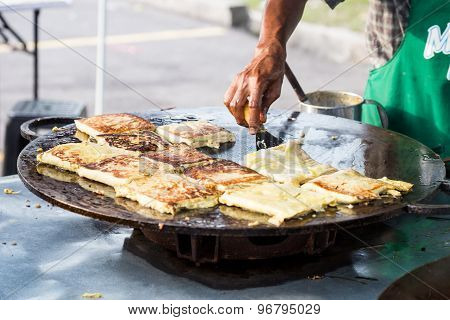 Vendor preparing traditional murtabak cuisine at street bazaar in Malaysia during Muslim fasting mon