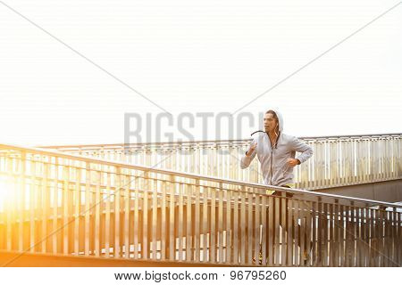 Sporty man working out at early morning while run up the bridge with orange sunrise on background