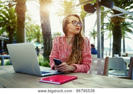 Attractive female freelancer hold smart phone while sitting at wooden table front open computer