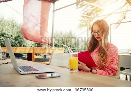 Charming young creative woman work on laptop while having breakfast in modern coffee shop