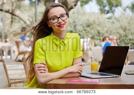 Pretty female sitting at the coffee shop with laptop computer open notebook with blank copy space