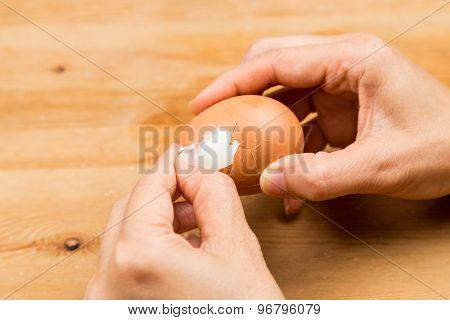 Fingers peeling hard boiled egg on wooden table