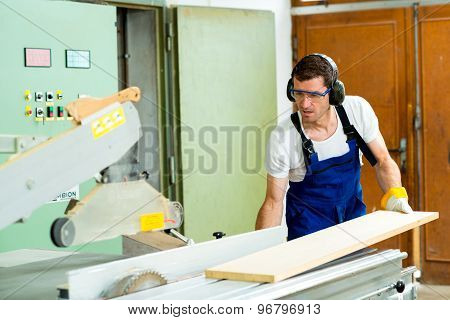Two Worker In A Carpenter's Workshop Using Saw