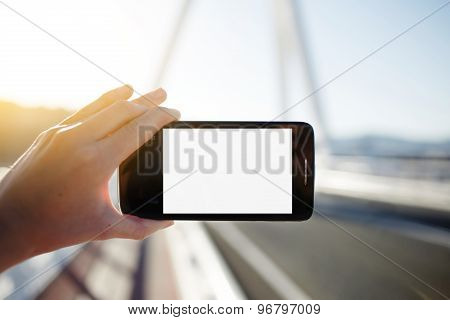 Female hand holding empty digital screen smartphone while taking a photograph of landscape