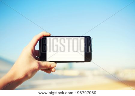 Tourist woman holding cell phone while taking a photograph of landscape in summer travel