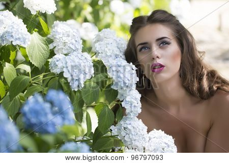 Portrait Of Attractive Woman And Blue Flowers