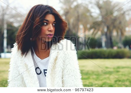 Portrait of attractive afro american woman with brunette hair sitting in the park with copy space
