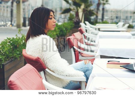 Pretty female hipster sitting on the terrace of sidewalk cafe with palm tree on background