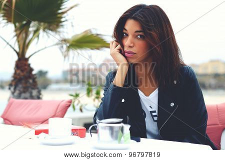 Attractive fashionable female posing to the camera while sitting in modern sidewalk cafe terrace