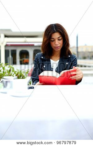 Beautiful student female engage leisure time for reading while sitting at the table of coffee shop