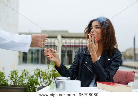 Attractive female hipster smiling at sidewalk cafe while waiter man lights up a cigarette for her