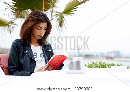 Attractive afro american woman enjoying a interesting book or novel while sitting at cafe terrace