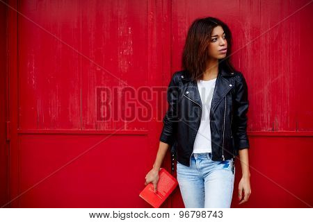 Young brunette woman holding book in the hand while strolling in the city at her recreation time