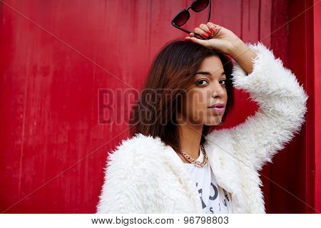 Portrait of fashionable afro american woman looking to you while holding sunglases in the hand