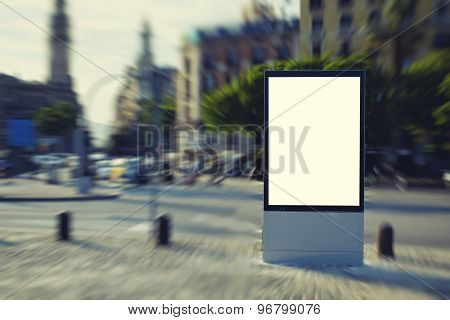 Public information board in blurred town advertising at beautiful sunny day