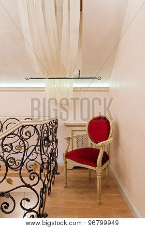 Red Classic Chair In The Hallway And Wrought Iron Railing