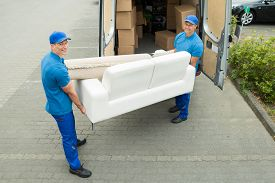 stock photo of moving van  - Two Happy Male Workers Putting Furniture And Boxes In Truck - JPG