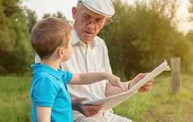foto of finger  - Closeup of senior man reading newspaper and cute child pointing an article with his finger sitting over a nature background - JPG